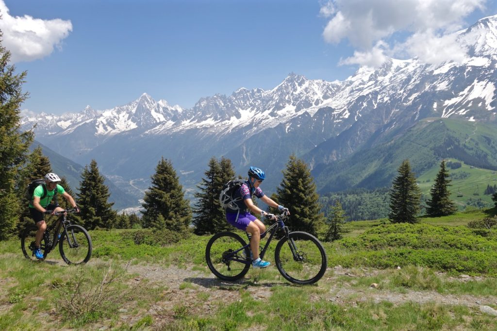Mountain Bikers ride past the Mont Blanc Massif