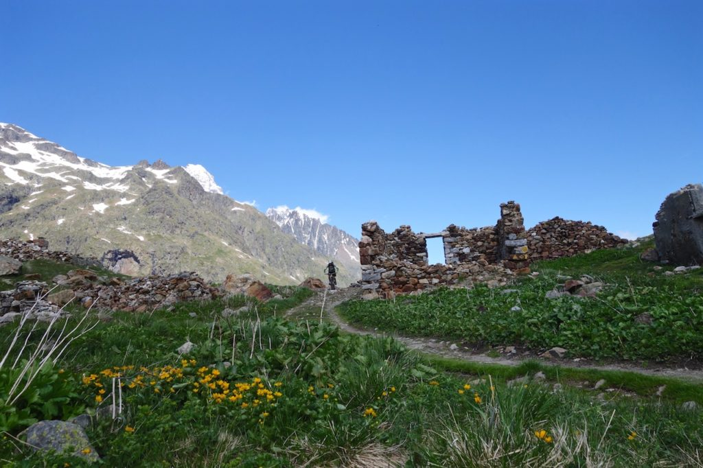 Mountain Biker riding past some old ruins Alps