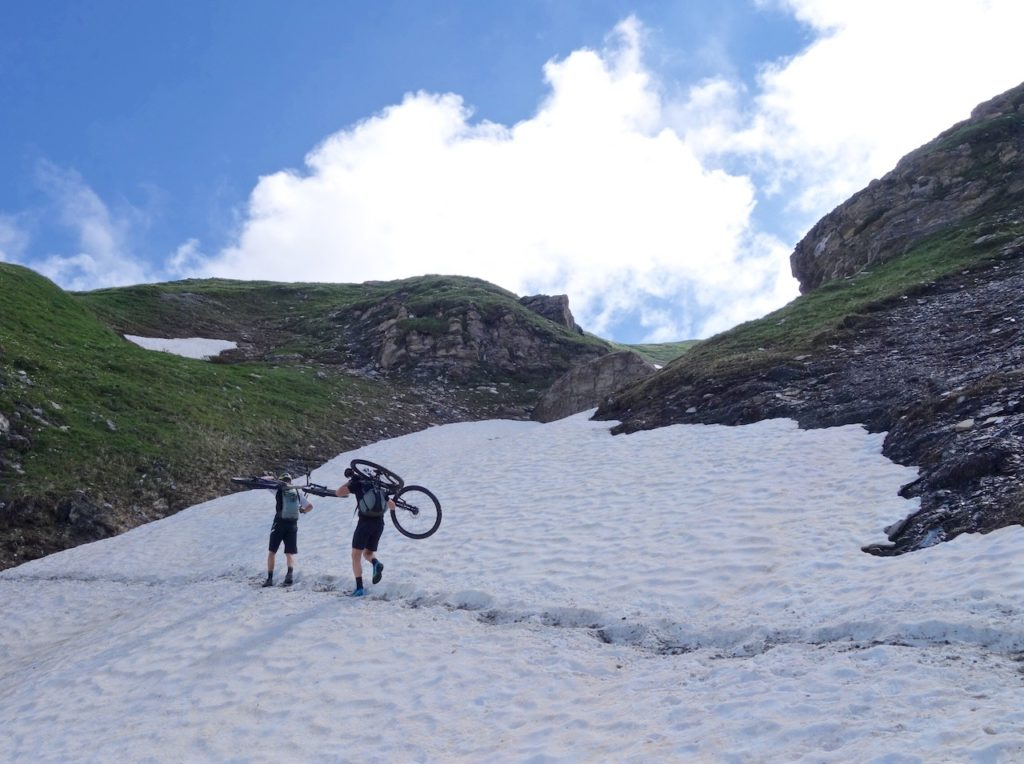 Two mountain bikers hiking the bike