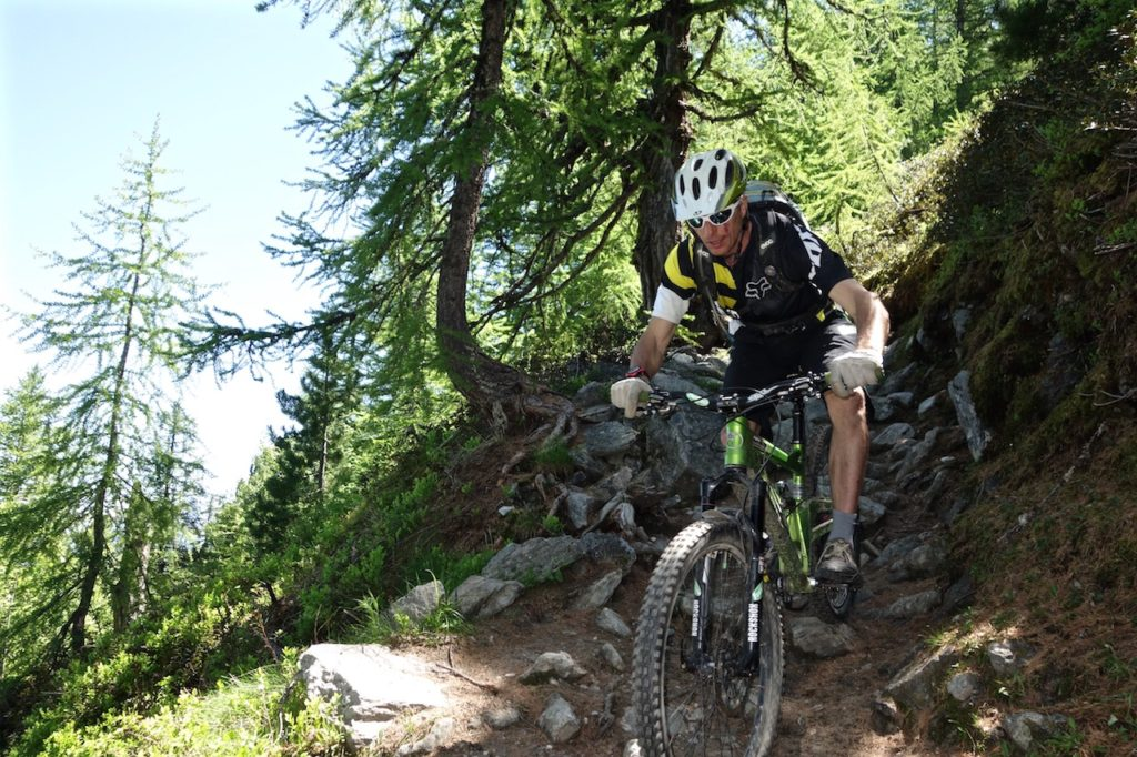 Mountain Biker Riding down rocks Alps